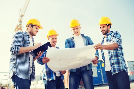 real estate planning: business, building, teamwork and people concept - group of smiling builders in hardhats with clipboard and blueprint outdoors