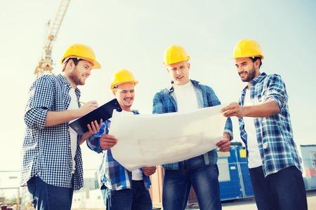negocio, construcción, trabajo en equipo y concepto de la gente - grupo de sonrientes constructores de cascos con el portapapeles y modelo al aire libre
