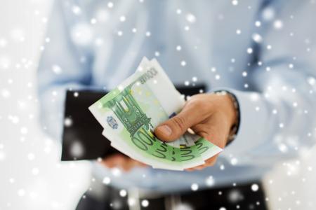 dinero euros: personas, negocios, finanzas y concepto del dinero - Cierre de negocios manos sosteniendo la cartera abierta con efectivo en euros sobre el efecto de la nieve