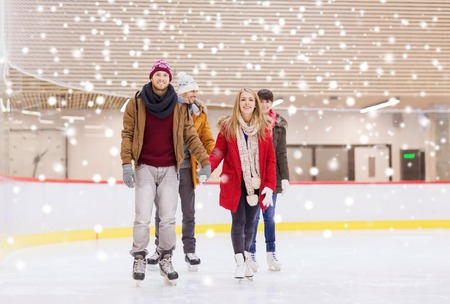 iceskates: people, friendship, sport and leisure concept - happy friends on skating rink
