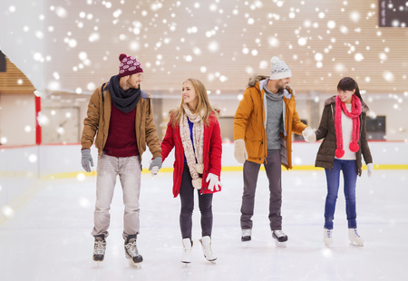 ice cold: people, friendship, sport and leisure concept - happy friends on skating rink