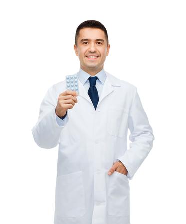 bata blanca: cuidado de la salud, la profesión, la gente y concepto de la medicina - sonriendo médico hombre en bata blanca con pastillas