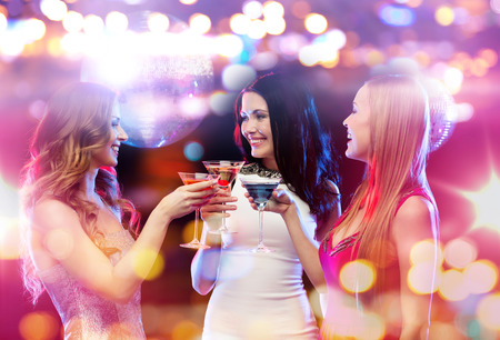 hen party: holidays, nightlife, bachelorette party and people concept - smiling women with cocktails at night club Stock Photo