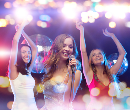 karaoke: party, holidays, nightlife, entertainment and people concept - concept - happy women with microphone singing karaoke and dancing at night club Stock Photo