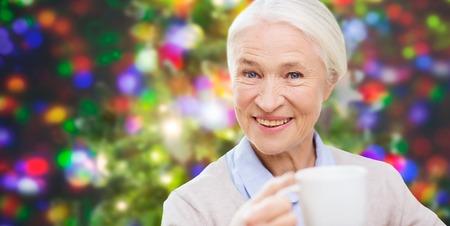 vacances, l'âge, la boisson et les gens notion - sourire heureux femme âgée avec tasse de thé ou de café sur fond lumières de Noël