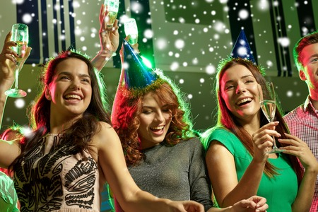 snow man party: new year party, holidays, celebration, nightlife and people concept - smiling friends with glasses of non-alcoholic champagne in club and snow effect Stock Photo