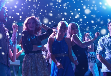 party people: new year party, holidays, celebration, nightlife and people concept - group of happy friends dancing in night club and snow effect