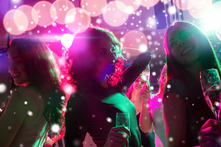 snow man party: new year party, holidays, celebration, nightlife and people concept - smiling friends with glasses of non-alcoholic champagne dancing at night club and snow effect Stock Photo