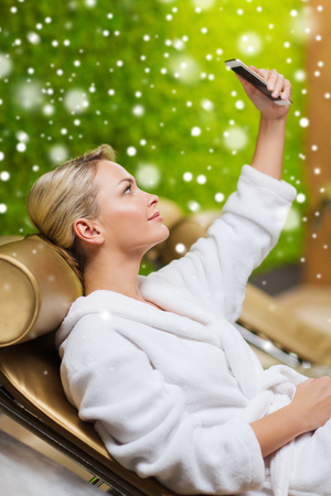 bath robe: people, beauty, lifestyle, technology and relaxation concept - beautiful young woman in white bath robe taking selfie with smartphone at spa with snow effect Stock Photo