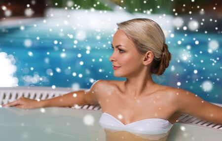 girls in bikini: people, beauty, spa, healthy lifestyle and relaxation concept - beautiful young woman wearing bikini swimsuit sitting in at poolside with snow effect