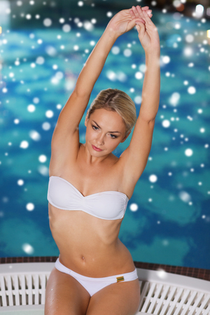 sexy female: people, beauty, spa, healthy lifestyle and relaxation concept - beautiful young woman wearing bikini swimsuit sitting with raised hands in jacuzzi at poolside with snow effect
