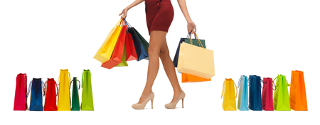 short sale: people, sale and consumerism concept - close up of woman in red short skirt and high heeled shoes with shopping bags Stock Photo