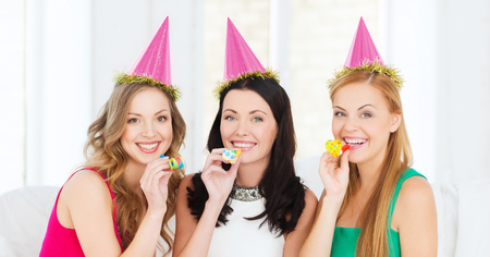 favor: celebration, friends, bachelorette party, birthday concept - three smiling women wearing pink hats and blowing favor horns Stock Photo