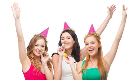 favor: celebration, friends, bachelorette party, birthday concept - three smiling women wearing pink hats and blowing favor horns and waving hands