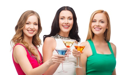 dress up: party, celebration, friends, bachelorette party, birthday concept - three beautiful women in evening dresses with cocktails Stock Photo
