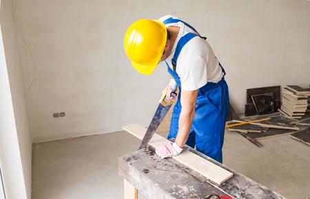 herramientas de carpinteria: construcci�n, carpinter�a, reparaci�n, trabajo en equipo y concepto de la gente - cerca de constructor con brazo de la sierra aserrado bordo en la mesa