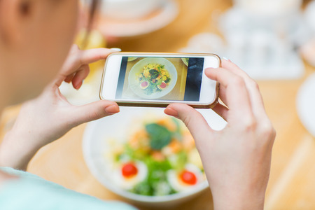 photographing: people, leisure and technology concept - close up of woman hands with smartphone taking picture of food at restaurant Stock Photo