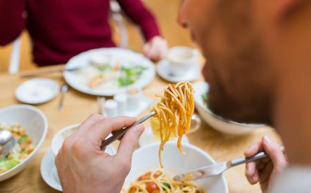 사람들은 레저 및 식품 개념 - 레스토랑이나 집에서 저녁 식사를 위해 사람을 먹는 파스타를 닫습니다