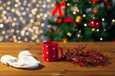 copa: días de fiesta, navidad, invierno y concepto de las bebidas - cerca de la taza de té con las manoplas y la decoración de navidad en la mesa de madera