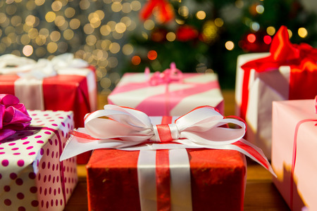 celebration: christmas, holidays, presents, new year and celebration concept - close up of gift boxes over christmas tree lights Stock Photo