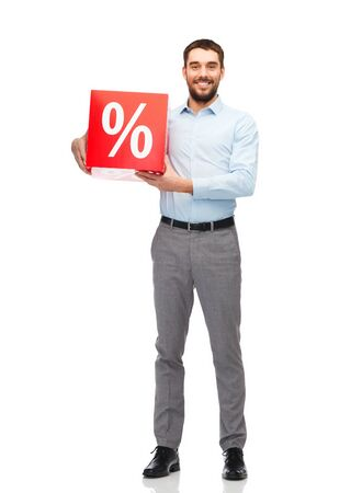percentage sign: people, sale, shopping, discount and holidays concept - smiling man holding red percentage sign Stock Photo