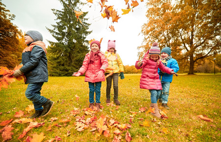 meadows: childhood, leisure, friendship and people concept - group of happy kids playing with autumn maple leaves and having fun in park