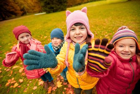 personas saludando: la infancia, el ocio, la amistad y el concepto de la gente - grupo de niños felices que agitan las manos en parque del otoño