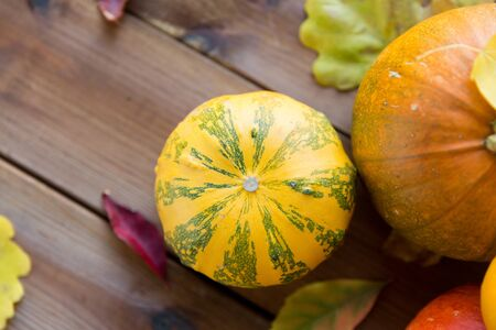 edible: harvest, season, advertisement and autumn concept - close up of pumpkins and leaves on wooden table at home