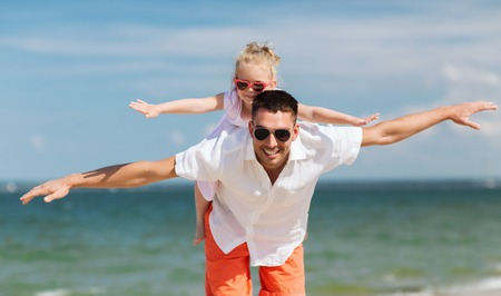 happy kid: family, travel, vacation, adoption and people concept - happy father with little girl in sunglasses having fun on summer beach Stock Photo