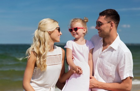 preteens beach: family, vacation, adoption and people concept - happy man, woman and little girl in sunglasses on summer beach
