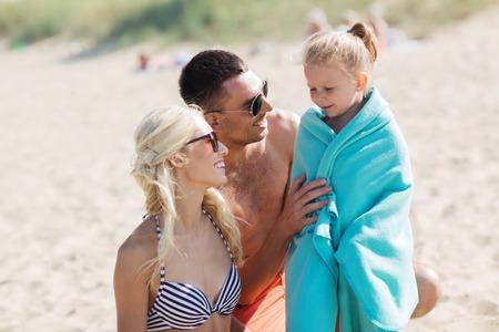 toalla: familia, vacaciones, adopción y Concepto - hombre feliz, mujer y niña en manta o una toalla en la playa de verano