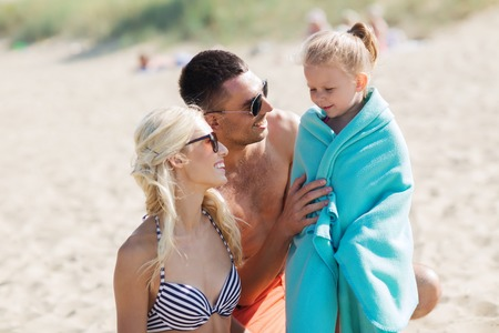 towel: family, vacation, adoption and people concept - happy man, woman and little girl in blanket or towel on summer beach Stock Photo