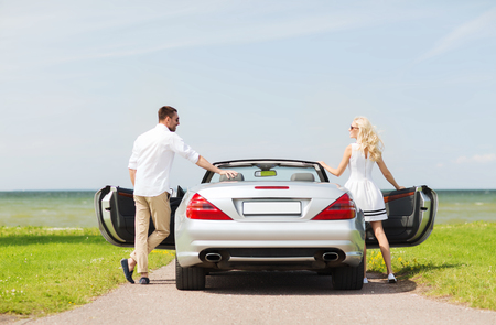 near side: transport, travel, road trip and people concept - happy man and woman near cabriolet car at sea side Stock Photo