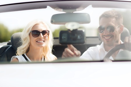 car navigation: road trip, leisure, travel, technology and people concept - happy man and woman driving car and using gps navigation system