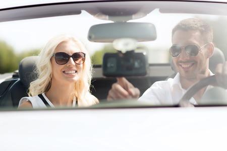 navegacion: viaje por carretera, el ocio, los viajes, la tecnología y el concepto de la gente - hombre feliz y mujer que conducía el auto y utilizar el sistema de navegación GPS