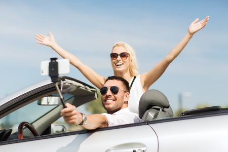 drive car: road trip, leisure, couple, technology and people concept - happy man and woman driving in cabriolet car and taking picture with smartphone on selfie stick Stock Photo