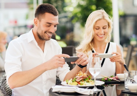 family vacation: love, date, technology, people and relations concept - happy couple with smatphone taking picture of food at restaurant