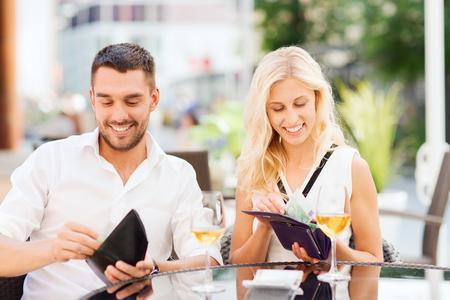 現金お金の財布とワインで幸せなカップル ガラス レストランで支払う法案の日付、人々、支払い、経済的自立の概念- 写真素材