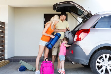 packing: transport, leisure, travel, road trip and people concept - happy family packing things into car at home parking