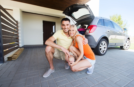 private insurance: transport, leisure, family and people concept - happy couple hugging at home car parking space Stock Photo