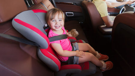 car seat: family, transport, safety, road trip and people concept - happy little girl sitting in baby car seat and father driving