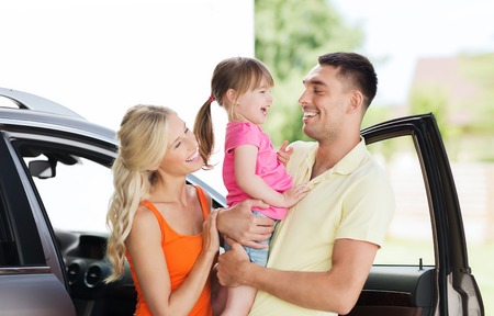 family, transport, leisure and people concept - happy man, woman and little girl with car laughing at home parking space Foto de archivo