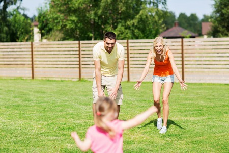 children running: family, happiness, adoption and people concept - happy little girl running towards father and mother outdoors Stock Photo