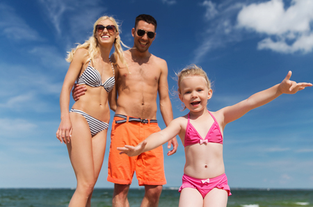 little child: family, childhood, travel and people concept - close up of happy man, woman and little girl having fun on summer beach Stock Photo
