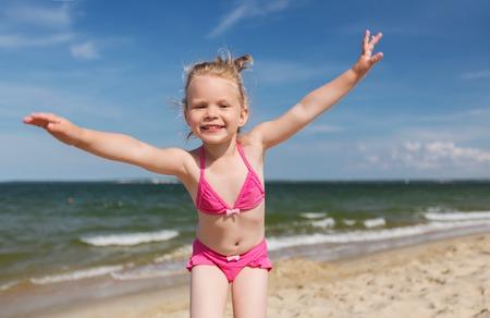 petite fille maillot de bain: l'été, l'enfance, les vacances et les gens concept - petite fille heureuse en maillot de bain amusant sur la plage