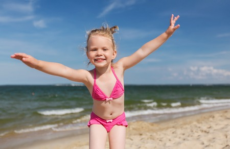 little girl smiling: summer, childhood, vacation and people concept - happy little girl in swimwear having fun on beach