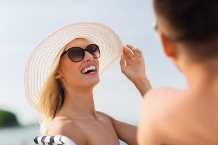 parejas romanticas: concepto de amor, los viajes, el turismo, el verano y la gente - sonriente pareja en tomar el sol de vacaciones en la playa