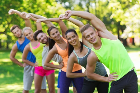 working out: fitness, sport, friendship and healthy lifestyle concept - group of happy teenage friends or sportsmen exercising and stretching at boot camp Stock Photo