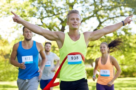 win: fitness, sport, victory, success and healthy lifestyle concept - happy man winning race and coming first to finish red ribbon over group of sportsmen running marathon with badge numbers outdoors Stock Photo