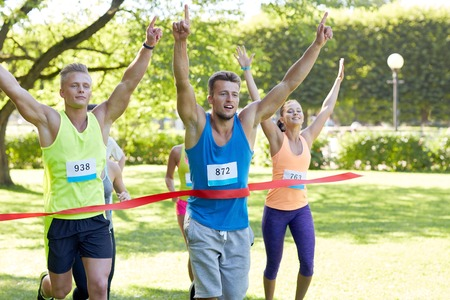 sports winner: fitness, sport, victory, success and healthy lifestyle concept - happy man winning race and coming first to finish red ribbon over group of sportsmen running marathon with badge numbers outdoors Stock Photo